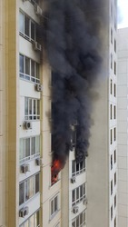 Blurry burning fire with black smoke from windows of building. Accident due arson in protests