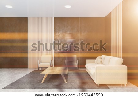 Blurry businessman walking in modern office waiting room with gray and wooden walls, concrete floor, comfortable beige sofas and armchairs near coffee table. Toned image #1550443550