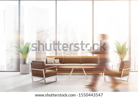 Blurry businessman walking in panoramic office waiting room with concrete floor, comfortable gray sofa and armchairs near round coffee table. Toned image #1550443547