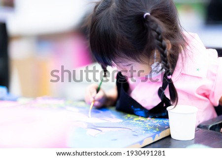 Blurry child do art on canvas in classroom. Kid paint watercolor in class with great intentions. Asian girl pulls mask under her chin due to being uncomfortable. Student aged 3-4 years. In cloudy day. Stock photo ©