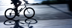 Blurry cyclist silhouette and shadow on a  bike path  in sunset, panning shot