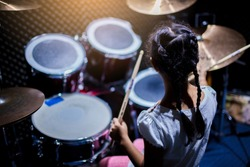 Blurry drum set and Asian girl learning and play it with wooden drumsticks in music room. The concept of musical instrument, Top view to drum player.