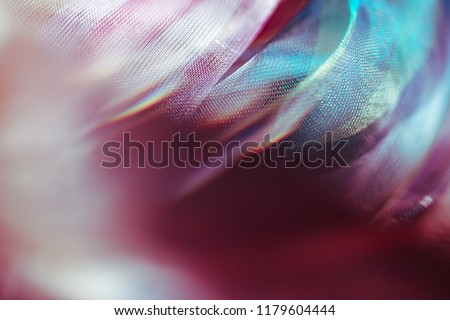 Blurry extreme close up macro of chiffon fabric. Beautiful sensual shapes colorful background. Real optical bokeh effect. Soft, delicate gentle pastel colors. Elegant decorative mesh textile backdrop