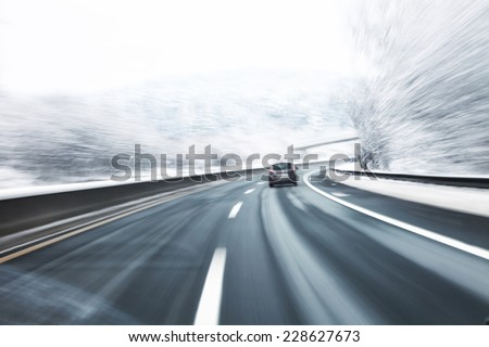 Blurry fast turn at the icy snow road with one car in the foreground. Motion blur visualizies danger of the high speed and dynamics.