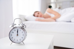 Blurry focus photo of charming lady sleeping bed white sheets blanket calm sure metal alarm clock ring at seven o'clock work oversleep 12 noon house monday bedroom indoors