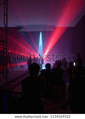 Blurry image and out of focus : Behind the scenes of video shooting production crew team silhouette and camera equipment in studio, Red laser beam