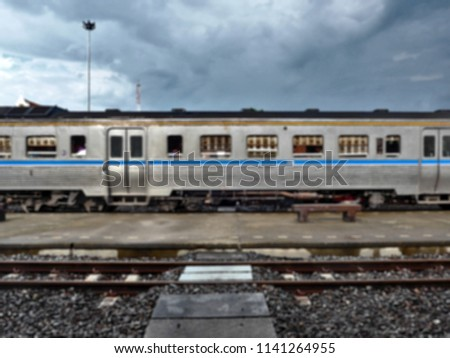 Blurry image and out of focus with dry brush filter : The old blue and silver wagon with windows of train parked at a station platform in  Thailand  #1141264955