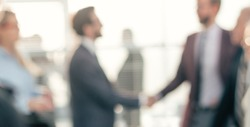 blurry image of a handshake of business people at a meeting in the office.