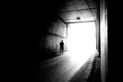 Blurry image of a human silhouette in a tunnel. A man going to the bright light in blur.