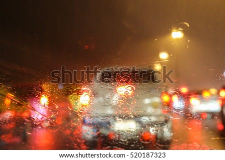 Blurry image of inside cars with bokeh lights with traffic jam and raining on night time for background usage.