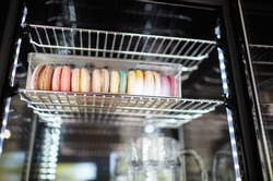 Blurry image of Showcase in cafe shop. Colorful macaroons in box on the shelves of a window of a street restaurant