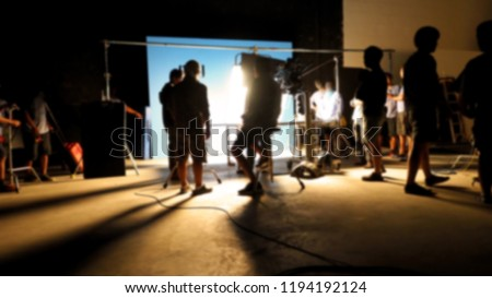 Blurry images of making video production shooting studio in silhouette which have professional equipment such as camera, tripod and blue screen backdrop set for chroma key technique in post process