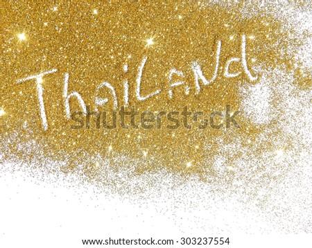 Blurry inscription Thailand on golden glitter sparkles on white background
