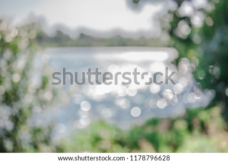 Blurry lake in the park, green environment, bleu water and sky, defocused photo, bokeh effect