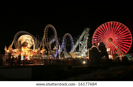 Blurry / long exposure image of a brightly lit amusement park rides