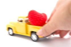 Blurry mini toy car and red heart in woman hand on white background
