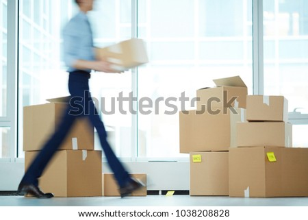 Blurry motion of businessman carrying boxes from one office to another during relocation