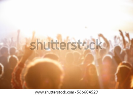 Blurry music festival with crowded dance floor in nightclub.Big live music show in night club.People have fun on concert.Huge concert crowd on fest.Fans audience wave hand to favorite singer sing song