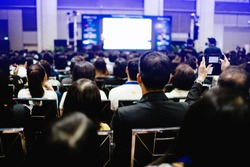 Blurry of auditorium for shareholders' meeting or seminar event with projector and white screen, many business people listening on the conference. blurred background of many people.