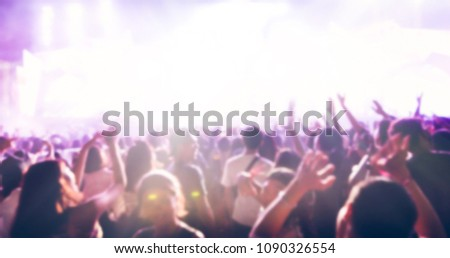blurry of silhouettes of concert crowd at Rear view of festival crowd raising their hands on bright stage lights #1090326554
