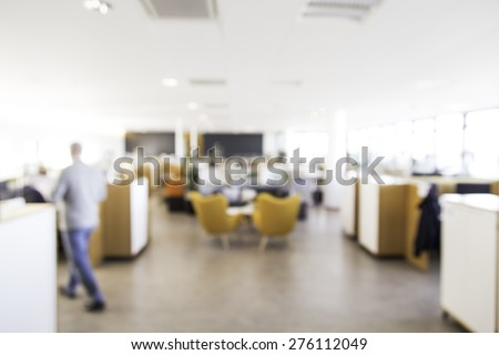 Blurry office with man out of focus walking away, great for use in designs for business or office settings