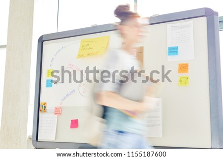 Blurry outline of girl passing by whiteboard while hurrying for or after class