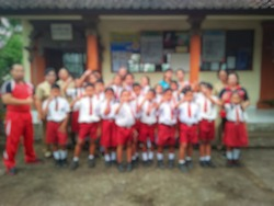 blurry photo of elementary school students and teachers in the school yard