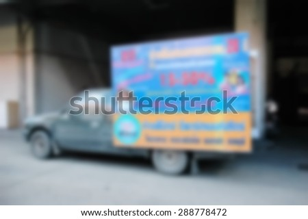 Blurry photo of light weight truck carry advertising board at the rear of car represent the media advertising concept related idea.