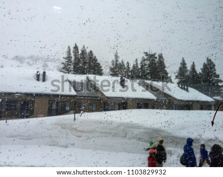 Blurry picture of houses in the winter and people walking by. Picture through a window on a rainy day.