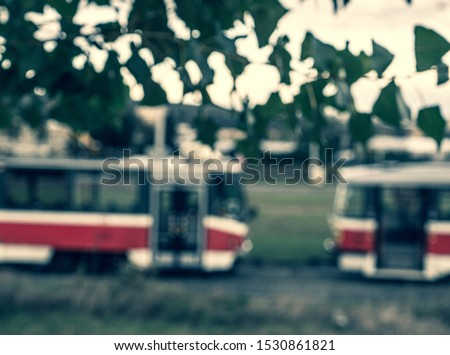 Blurry picture of two red tram carriages in Brno city with blurry leaves and intense sunlight in the top. Intentionally blurry transportation vehicles behind blurry green-white foreground elements.