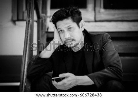 Blurry portrait of businessman with smart phone outdoor,Frustrated #606728438