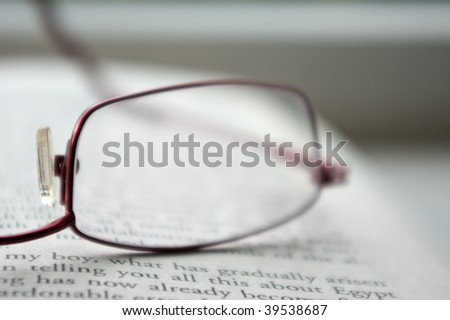Blurry reading glasses on an open book
