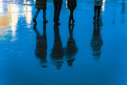 Blurry reflection legs and shadows, silhouettes of the men and women in the wet sidewalk, in a puddle, walk on a rain. Concept of seasons, weather, lifestyle