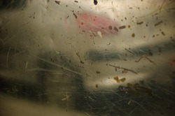 Blurry reflection of a car on old metal grungy surface with rusty scratches and dirty stains. Abstract background.