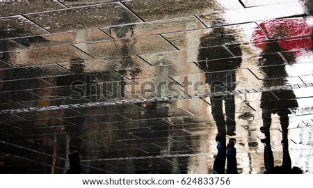 Blurry reflection silhouette of a woman and a man walking in the rain in the city pebbled sidewalk