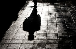 Blurry shadow and silhouette of a man standing in the night on wet city street sidewalk with water reflection in black and white