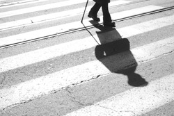 Blurry shadow and silhouette of a senior man crossing the street and zebra crosswalk with  a cane in black and white