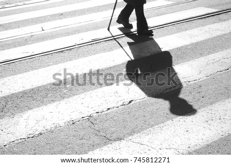 Blurry shadow and silhouette of a senior man crossing the street and zebra crosswalk with  a cane in black and white #745812271