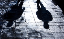 Blurry shadow and silhouette of two men standing in the night on wet city street sidewalk with water reflection in black and white