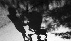 Blurry shadow of a woman with postpartum depression pushing a baby trolley on the cracked asphalt suburban park road in black and white