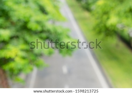 Blurry & Top view, small road in urban downtown area which both sides of sidewalk covered with fresh green trees, a part of sustainable urbanization to better air quality, wellness and quality of life