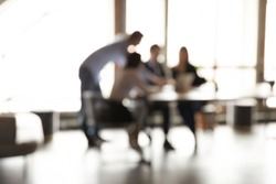 Blurry view of diverse colleagues gather at desk cooperate discuss business ideas together, multiracial employees businesspeople brainstorm work in group team on project in office, teamwork concept