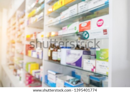 Blurry view of drug store and pharmacist. Blurred clean pharmacy with medicine on shelves. Defocus white drugstore #1395401774