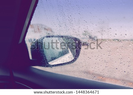 Blurry wet abstract glass background. Rear back view car mirror with rain drops during rainy bad weather. Sadness loneliness concept. Toned with retro vintage violet purple filters.