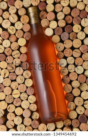 Blush Wine: A bottle of white zinfandel surrounded by corks standing on end filling the frame. Bottle has no label. #1349454692