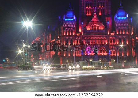 BMC head quarters mumbai with t he light trails of the traffic moving on the street.Famous architecture light up with colorful lights at night. Slow shutter speed ,camera on tripod ,blured vehicles