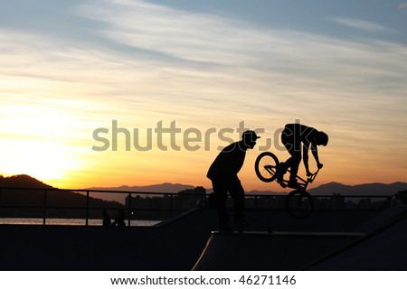 BMX Bike flying off the track with the sea, horizon and sunset in the background. Also shows the perfect silhouette of another guy looking amazed to the BMX.