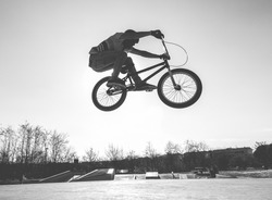 Bmx biker jumping in city skate park outdoor - Young trendy man performing skills and tricks with special bicycle - Extreme sport concept - Black and white editing