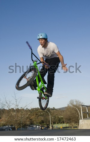 BMX rider jumps while doing bar spin