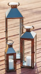 board a decorative candle holders on the pier. Three candle lanterns on the pier.